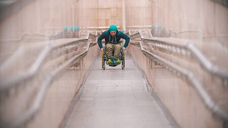 Disabled man in wheelchair going up the long special ramp set in the subway Banco de Imagens