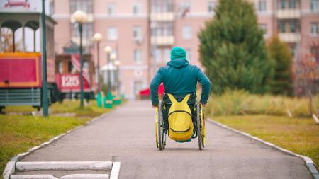 Disabled man in wheelchair rides on the footpath