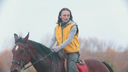 A woman in yellow jacket on a horse back Stock Photo