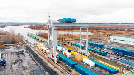 Cargo river port - A big industrial crane unloading the cargo from the freight carriages on the ground. Aerial view Stok Fotoğraf