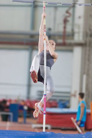 Pole vaulting indoors - young woman leaning on the pole and about to jump