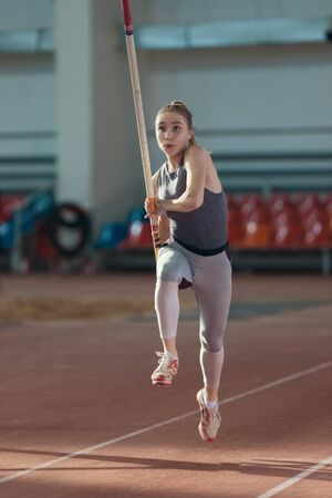 Pole vaulting indoors - young sportive woman with ponytail running with a pole in her hands Фото со стока