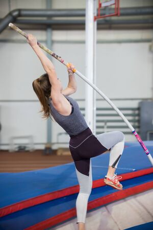 Pole vaulting indoors - young sportive woman with ponytail leaning on the pole and about to jump