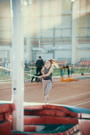 Pole vaulting indoors - young sportive woman with ponytail running with a pole in her hands - bright light on the background