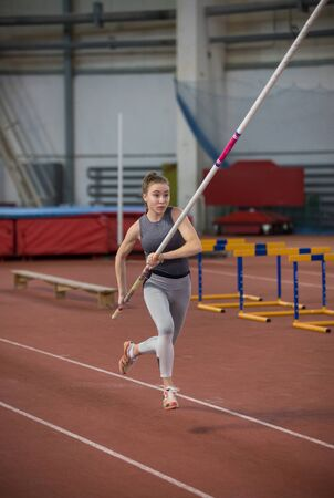 Pole vaulting indoors - young sportive woman running on the runway with a pole in the hands