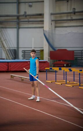 Pole vaulting indoors - young man in blue shirt standing on the runway holding a pole