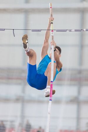 Pole vaulting indoors - young man jumping over the partition