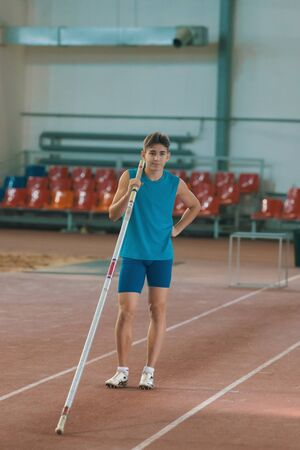 Pole vaulting indoors - young man posing for the camera holding a pole