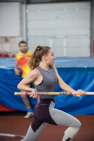Pole vaulting indoors - young sportive woman with ponytail running with a pole in the hands