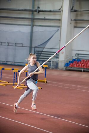 Pole vaulting indoors - young woman in leggins running with a pole in the hands