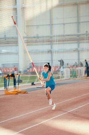 Pole vaulting indoors - young man in blue shirt running up before jumping with a pole