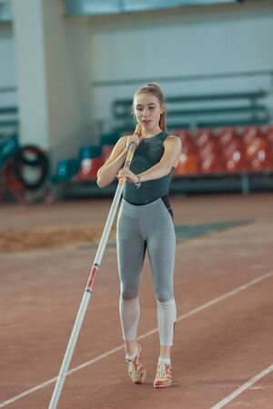 Pole vaulting indoors - young pretty woman in leggins posing for the camera holding a pole 写真素材