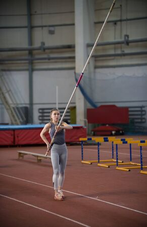 Pole vaulting indoors - young woman holding a pole looking up Banco de Imagens
