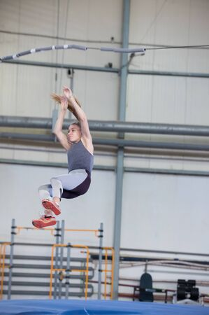 Pole vaulting indoors - young sportive woman with a ponytail falling down after the jump Banco de Imagens