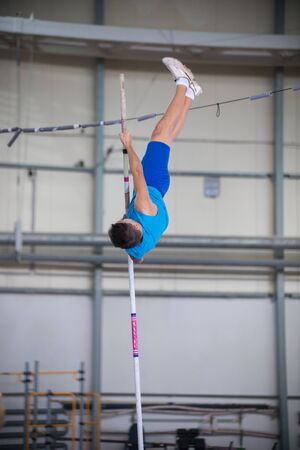 Pole vaulting indoors - young man jumping over the partition - leaning on the pole and about to jump