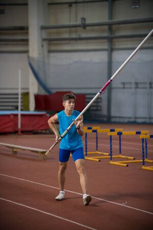 Pole vaulting indoors - young man standing on the runway holding a pole
