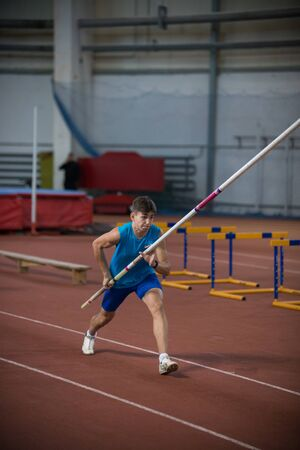 Pole vaulting indoors - young man running on the runway holding a pole Banco de Imagens