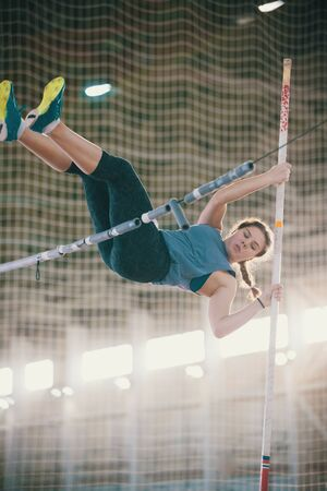Pole vaulting indoors - young woman with pigtails jumping over the partition - bright lighting on the background Banco de Imagens