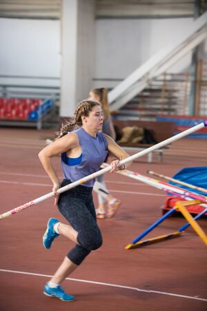Pole vaulting indoors - young woman with pigtails running with a pole in the hands