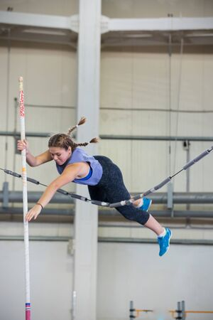 Pole vaulting indoors - young woman with pigtails jumping over the partition trying not to touching it