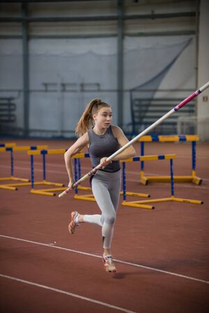 Pole vaulting indoors - young woman running with a pole in the hands Banco de Imagens
