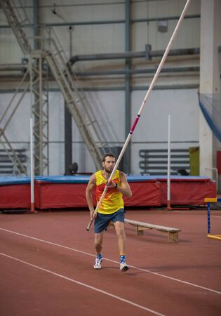 Pole vaulting indoors - a man in yellow shirt standing on the track with a pole