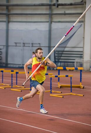Pole vaulting indoors - a athletic man in yellow shirt running on the track with a pole in the stadium
