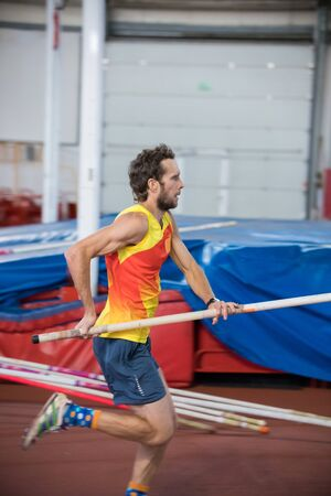 Pole vaulting indoors - a athletic man running on the track with a pole in the sports stadium Stockfoto