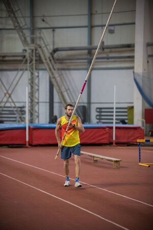 Pole vaulting indoors - a man standing on the track with a pole