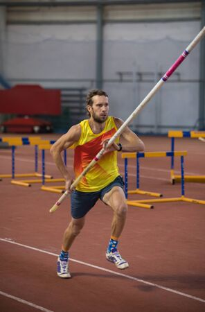 Pole vaulting indoors - a man running on the track with a pole