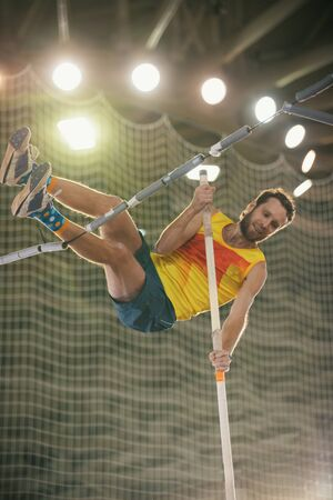 Pole vaulting in the sports stadium - an athletic smiling man in yellow shirt jumping over the bar