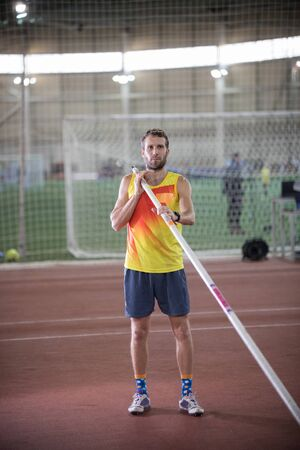 Pole vaulting in the sports stadium - an athletic man in yellow shirt posing for the camera Stockfoto