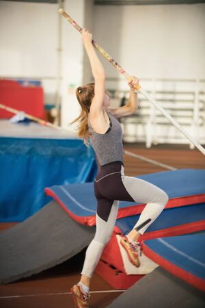 Pole vaulting in the sports stadium - young sportive woman with ponytail in grey leggins about to jump over the bar
