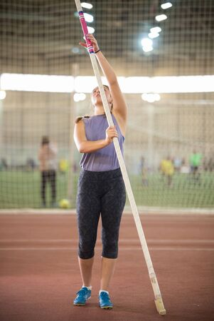 Pole vault training in the sports stadium - young sportive woman with pigtails standing on the track holding a pole