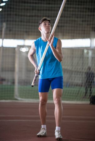 Pole vault training in the sports stadium - young man standing on the track holding a pole