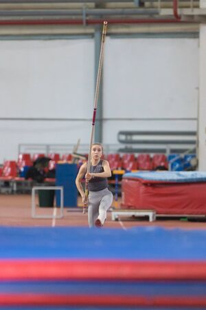 Pole vaulting - woman in a gray suit is running with pole in hands