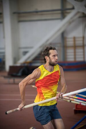 Pole vaulting indoors - an athletic man running on the track with a pole Stockfoto