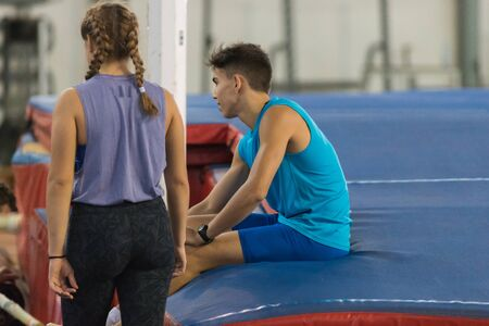 Guy is sitting on the mat near girl is standing Stockfoto