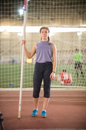Pole vault training in the sports stadium - young woman with pigtails standing on the track holding a pole