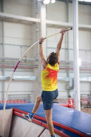 Pole vaulting indoors - a athletic man jumping over the bar - the pole flexing under the weight