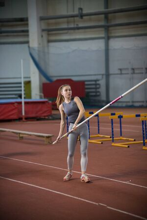 Pole vaulting - young woman is standing with pole in hands Banco de Imagens