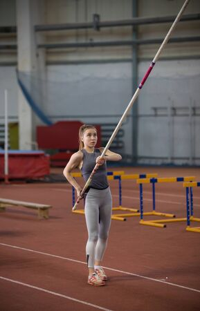 Pole vaulting - pretty woman raised the long pole up