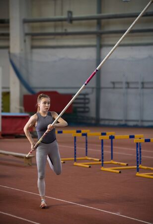 Pole vaulting - pretty woman is warming with long pole Banco de Imagens