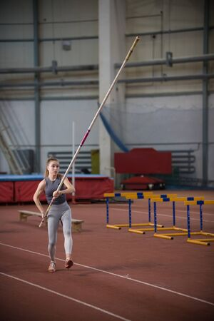 Pole vaulting - woman is going to run with a long pole in her hands