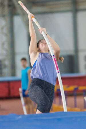 Pole vaulting - young woman in a purple shirt is pushing off the floor with a pole and jumping