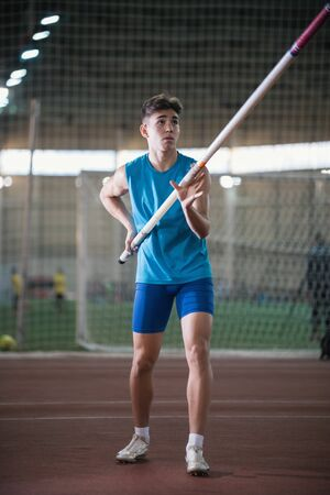 Pole vault training in the sports stadium - young man standing on the track holding a pole and looking up