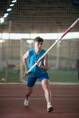Pole vault training in the sports stadium - young man running on the track holding a pole