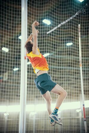 Pole vaulting indoors - a sportive man falling down after the jump - bright lights on the background