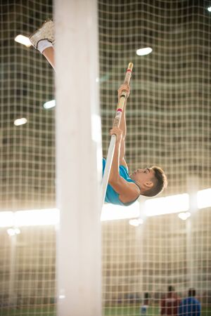Pole vaulting training - young fit man jumping over the bar Banco de Imagens