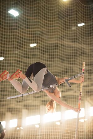 Pole vaulting in the sports stadium - young sportive woman with ponytail jumping over the bar Banco de Imagens